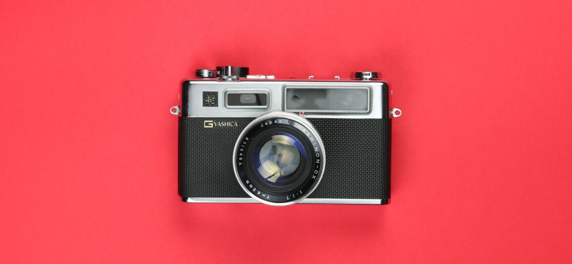 A camera rests on a red backdrop
