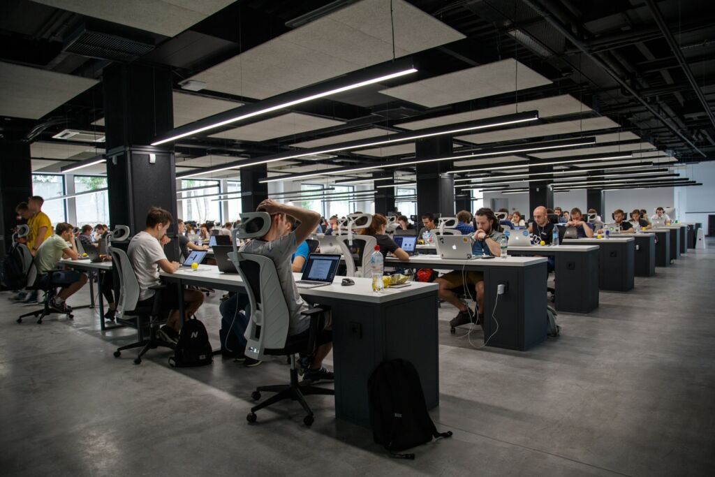 People sit at their desks in a large office.