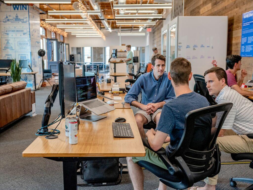 Three men sit at office desks while in conversation.