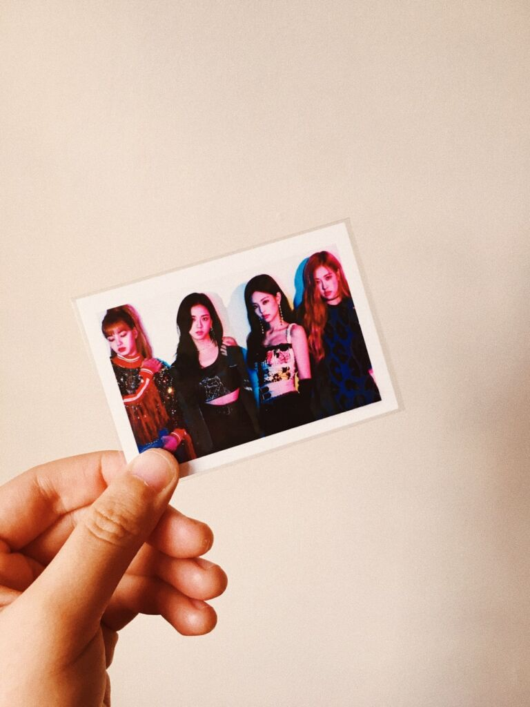A hand holds a photograph of four women posing for the camera.