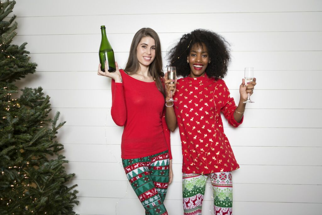 Two women stand next to a Christmas tree in Christmas decorated clothing holding drinks.