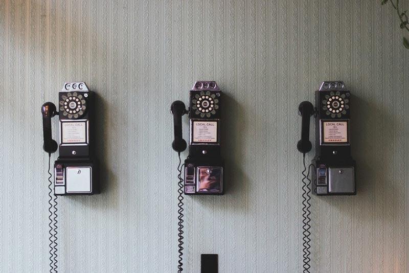 line of three antique phones